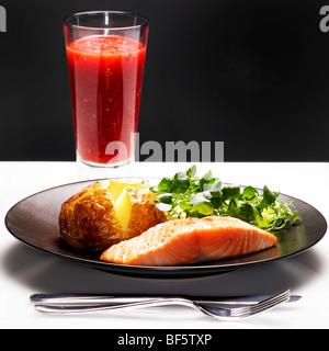 Lachsfilet mit Ofenkartoffel, grüne Blatt Salat und Fruchtsaft. Stockbild