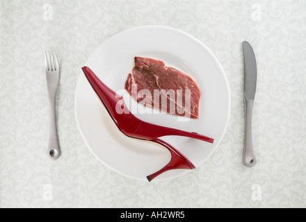 rote high-Heel mit Fleisch und Utensilien auf weißen Teller, Studio gedreht Stockbild