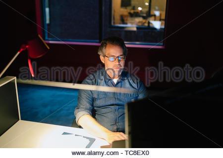 Engagierte Unternehmer spät am Computer in dunklen Büro arbeiten Stockbild
