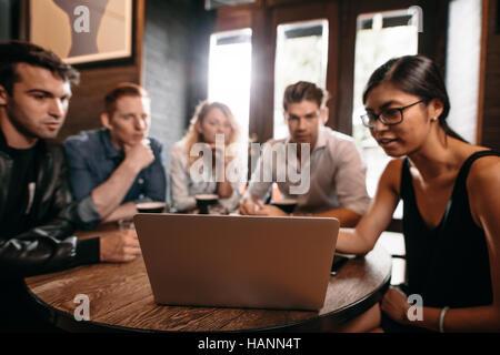 Gruppe von Freunden an Cafétisch sitzen und mit Blick auf Laptop. Junge Männer und Frauen im Coffee Shop Stockbild