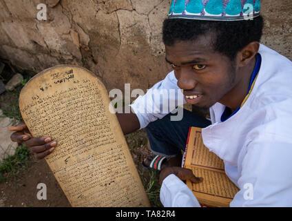 Mann mit einem Holzbrett für das Schreiben von Koran in einer Koranschule, Tonkpi Region, Mann, Elfenbeinküste Stockbild
