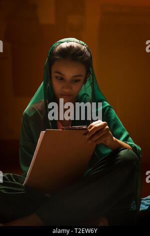 Ländliche Mädchen schreiben auf Prüfung pad unter Licht Stockbild