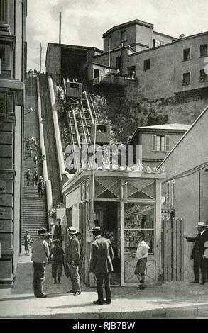 Eine der vielen steilen Standseilbahnen oder Aufzüge in der Stadt Valparaiso, Chile, Südamerika, mit einer Reihe von steilen Treppen neben. Stockbild