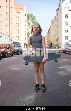 Mädchen in der Straße stehen, halten skateboard Stockbild