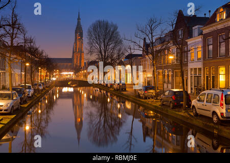 Die Kirche spiegelt sich in einem Kanal in Delft in den Niederlanden in der Nacht. Stockbild