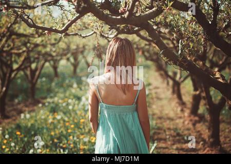 Frau alleine in einem Obstgarten. Frieden und Ruhe Stockbild