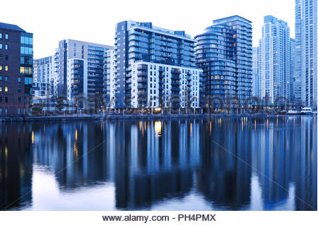 London Docklands Skyline - moderne Wohn- und Wolkenkratzer im Wasser in der Dämmerung widerspiegelt. Auf der Isle of Dogs in East London, Großbritannien. Stockbild