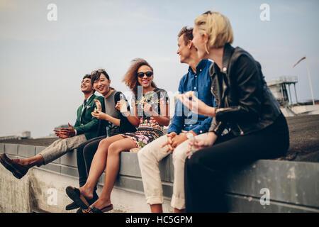 Glückliche junge Menschen feiern auf Dach mit Getränken. Gemischtrassig Männer und Frauen auf der Stockbild
