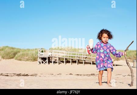 Mädchen spielen am Strand Stockbild