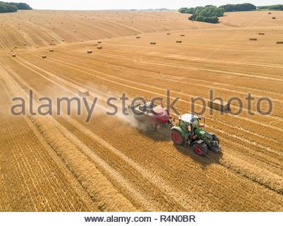 Antenne Overhead von Traktor Ballenpresse Strohballen in Feld nach der Weizenernte im Sommer auf der Farm Stockbild
