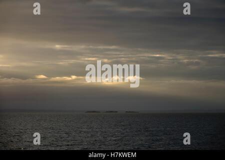 See mit drei kleinen Inseln in der Dämmerung. Ruhige und schöne Natur Hintergrund. Stockbild