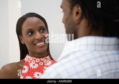 Afrikanischer Mann lächelnd an Freundin Stockbild