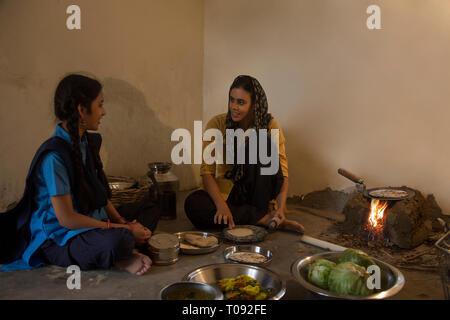 Frau im ländlichen Küche kochen sitzen auf Brennholz mit Utensilien und Gemüse auf dem Boden und im Gespräch mit ihrer Tochter. Stockbild