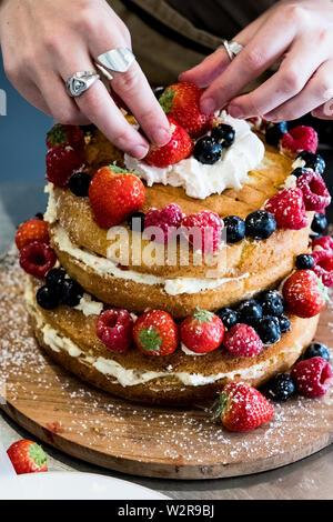 Eine Frau Koch asembling eine Schicht Kuchen mit Sahne und frischem Obst, Erdbeeren und Blaubeeren. Stockbild