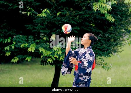 Mädchen im Kimono spielen mit Papier-Ballon Stockbild