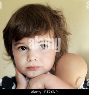 Vier Jahre altes Mädchen eine Puppe hält Stockbild