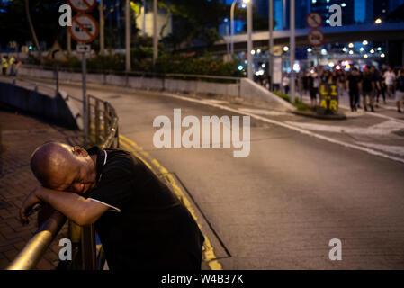 Ein Mann schläft, während ein Tausende Demonstranten nehmen Sie Teil einer Grosskundgebung fordert unabhängige Untersuchung Polizei Taktik in Hongkong. Stockbild