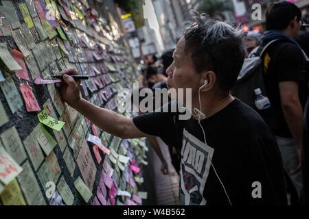 Ein Mann klebt ein Aufkleber Aufkleber mit Nachrichten, die gegen die Auslieferung Bill und pro-Demokratie in einem Lennon-mauer in Wan Chai. Hong Kong Demonstranten versammelten für ein weiteres Wochenende der Proteste gegen die umstrittene Auslieferung Rechnung und mit einer wachsenden Liste von Beschwerden, die der Aufrechterhaltung des Drucks auf Chief Executive Carrie Lam. Stockbild