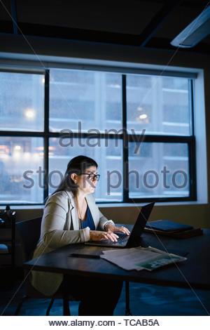 Engagierte Unternehmerin spät am Laptop arbeiten in dunklen Büro Stockbild