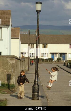 Kinder spielen in der Straße schwingen aus einer Lampe post Belfast Vorort Nordirland 1980 HOMER SYKES Stockbild