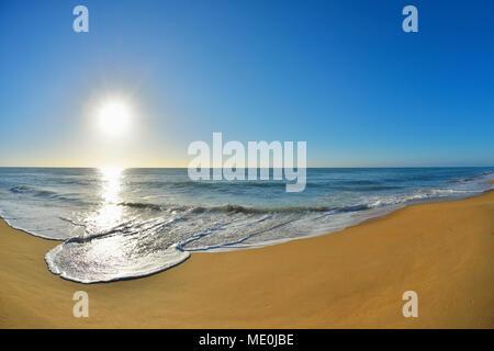 Surfen brechen auf der Küstenlinie von Ninety Mile Beach Paradise Beach mit der Sonne über den Ozean in Victoria, Australien, glänzend Stockbild