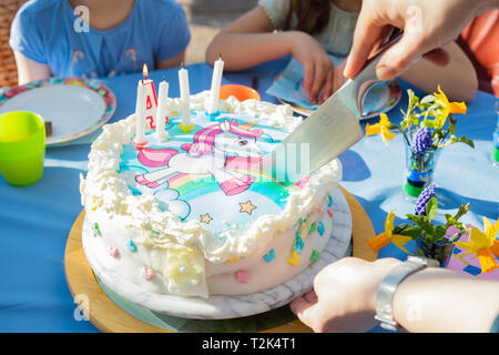 Schneiden eine Geburtstagstorte mit einem Einhorn Charakter. Stockbild
