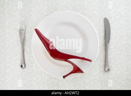 rote high-Heel mit Utensilien auf weißen Teller, Studio gedreht Stockbild