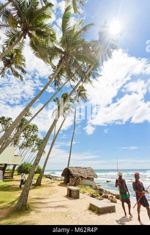 Koggala Beach, Sri Lanka, Asien - Dezember 2015 - Zwei einheimischen Fischer zu Fuß zum Strand angeln zu gehen Stockbild