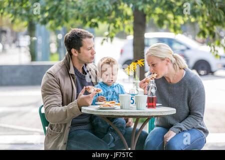 Eltern mit Sohn essen Kuchen im Straßencafé Stockbild