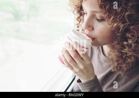 Nahaufnahme Porträt einer wunderschönen, jungen Frau mit blauen Augen und Lockige blonde Haare Getränke Kaffee oder Tee, während Sie in einer Reise Stockbild