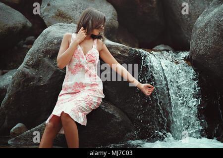 Junge Frau berühren einen Wasserfall. Sommer Kleid Stockbild