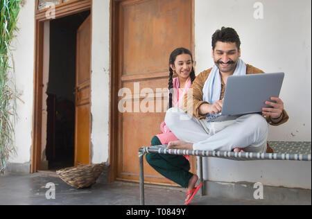 Happy Village Mann sitzt mit ihrer Tochter auf einem Feldbett, die ein Laptop. Stockbild
