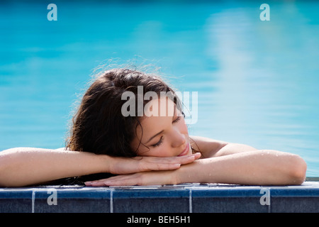 Junge Frau Nickerchen am Pool Stockbild