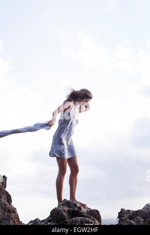 Frau stehend auf Felsen in der Nähe von Meer, Stoff im Wind zu halten. Stockbild