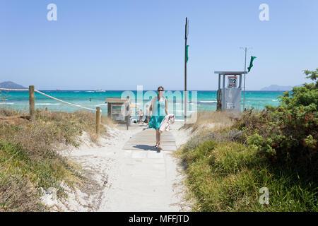 Platja de Muro, Mallorca, Spanien - AUGUST 2016 - eine junge Frau, die vom Strand von Platja de Muro Stockbild
