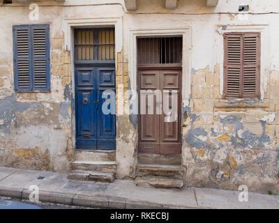 Außen in St. Julian's, Malta, blaue und braune Türen auf verfallene Häuser Stockbild
