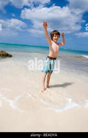 Ein kleiner Junge, springen auf der Strand, Cable Beach, Nassau, Bahamas, Karibik Stockbild