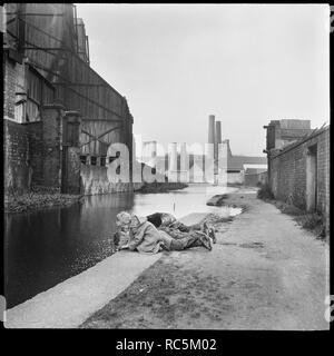 Caldon Canal, Joiner's Square, Hanley, Stoke-on-Trent, Staffordshire, 1965-1968. Kinder liegen auf dem Leinpfad Blick in die Gewässer der Caldon Canal gegenüber dem Strom arbeitet mit Trent arbeitet und Westwood Mühlen im Hintergrund. Stockbild