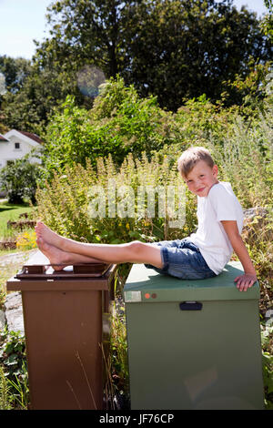 Junge, draußen zu sitzen Stockbild