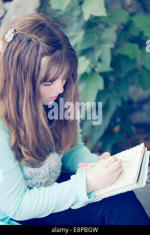 Porträt von Teenager-Mädchen (13-15) schreiben Stockbild