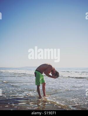 Mann, die Haare im Ozean spülen Stockbild