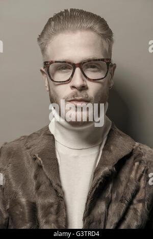 Studio-Porträt eines jungen Mannes mit Brille tragen eine Pelzjacke cool. Stockbild