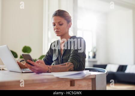 Aufnahme des jungen Frau liest SMS auf ihr Handy während der Arbeit am Laptop. Stockbild