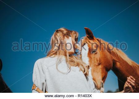 Low Angle View einer Frau mit einem Pferd unter einem klaren blauen Himmel Stockbild