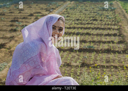 Junge lächelnde ländliche Frau sitzt in ihrer Landwirtschaft Feld über dem Kopf mit Sari. Stockbild