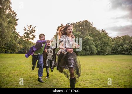 Kinder jagen eine Mädchen gekleidet wie ein Zombie Ballkönigin für Halloween-Nacht. Stockbild