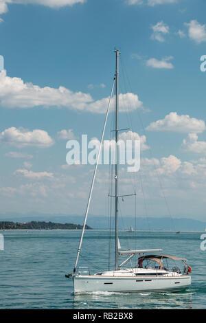 Schönes kleines Segelboot auf einem See in der Nähe der Küste Stockbild