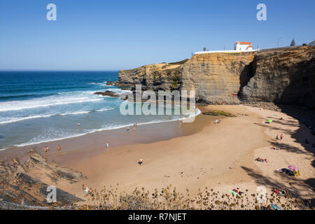 Klippe Kapelle von Igreja de Nossa Senhora do Mar mit Wellen des Atlantiks am Sandstrand in der Morgensonne brechen bei Zambujeira do Mar Stockbild
