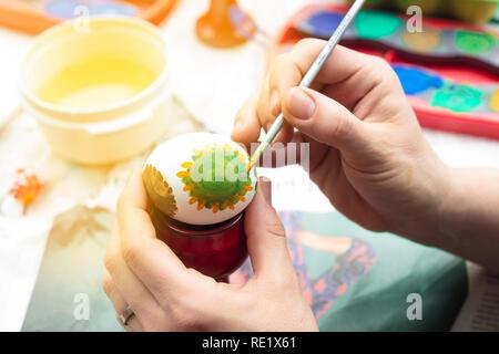 Detail der Frau Malerei ein Osterei mit Pinsel und Wasserfarben. Stockbild