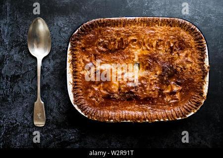Hohen Winkel in der Nähe der frisch gebackene Chicken Pie und silbernen Löffel. Stockbild